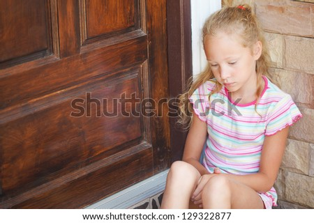 sad little girl sitting near a door on the background of an brick wall - stock photo