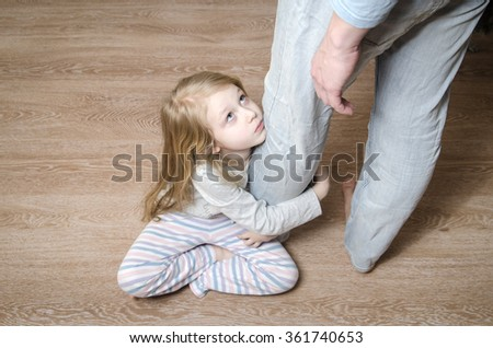 Sad little girl sitting on the floor and hugging her father's leg, top view - stock photo