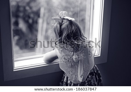 Sad little girl wearing angel fairy wings look outside from a home window. Concept photo of child abuse. - stock photo