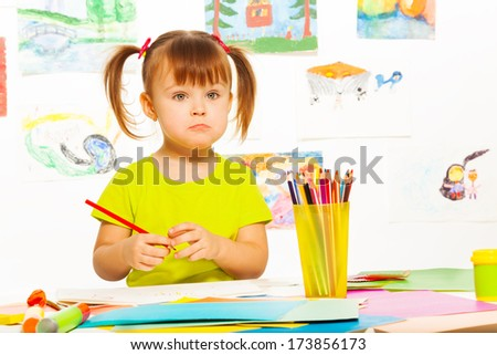Sad little girl with pencil in the early development class - stock photo