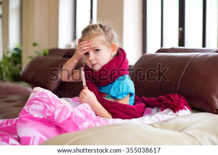 Sad little ill girl lies on sofa with thermometer and scarf on neck getting well of flu feeling bad - stock photo