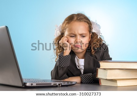 Sad Little Schoolgirl Sits At Table With Books Near Laptop On Blue Background - stock photo
