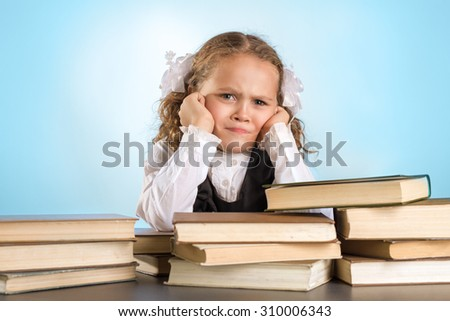 Sad Little Schoolgirl Sits At Table With Books On Blue Background - stock photo