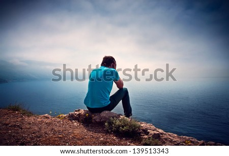 Sad lonely boy on a hill overlooking the sea - stock photo