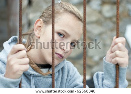 Sad lonely child is behind grid - stock photo