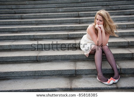 Sad lonely girl sitting on the steps - stock photo