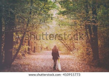 Sad Lonely Woman Walking Away into the Autumn Forest - stock photo