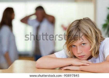 Sad looking boy with his arguing parents behind him - stock photo