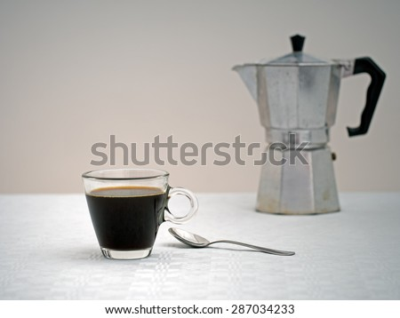 Sad looking coffee and old espresso machine, blurry, in distance.  Focus on cup. Coffee for one, loneliness concept. - stock photo