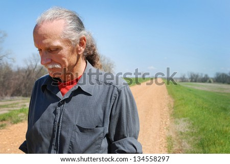 Sad looking man standing along a lonely dirt road - stock photo