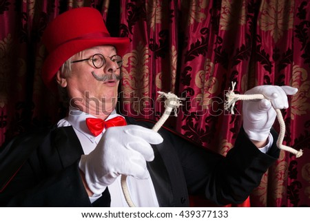 Sad magician holding a broken rope as his trick went wrong - stock photo
