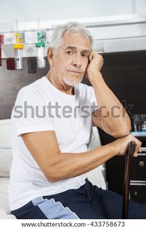Sad Male Patient Holding Cane At Rehab Center - stock photo