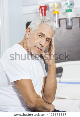 Sad Male Patient Sitting On Bed At Rehab Center - stock photo