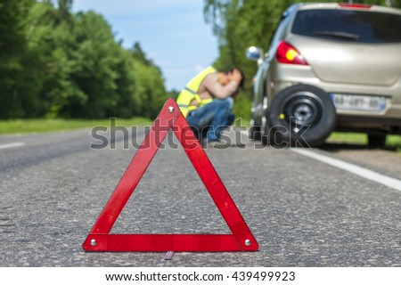 Sad man after breakdown, broken car and spare wheel on the roadside. Focus on red triangle warning sign - stock photo