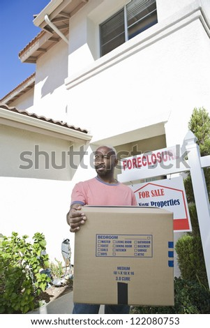 Sad man carrying cardboard box while moving out of the house - stock photo