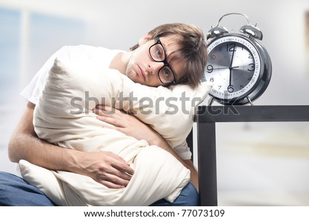 Sad man holding pillow - stock photo