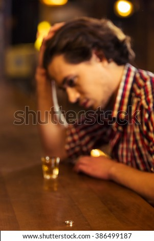 Sad man in casual clothes is leaning on bar counter in pub, a glass of alcoholic beverage near, in the foreground a wedding ring - stock photo