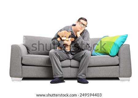 Sad man in pajamas holding a teddy bear seated on a sofa isolated on white background - stock photo