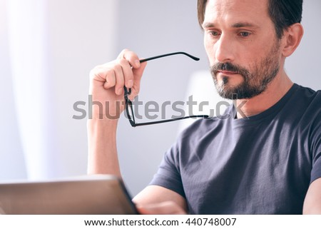 Sad man looking at screen of laptop - stock photo