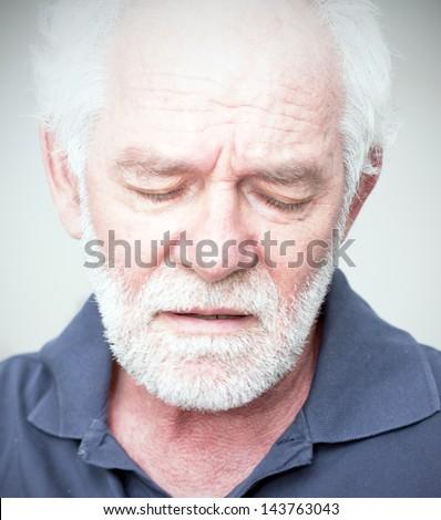 Sad man, looking down caucasian man with white beard - stock photo