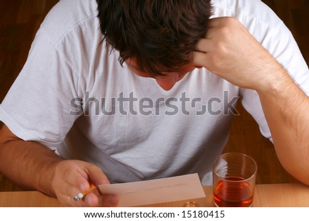 Sad man looking into the photo of a lost love (or a child) while consuming alcohol (conceptual) - stock photo