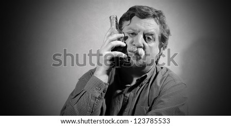 sad man put a bottle of whiskey to his cheek - stock photo
