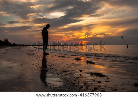 Sad man silhouette on the beach at sunset with the sun in the background  - stock photo