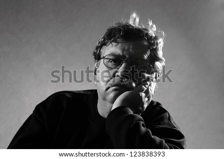 sad man sits, his head in his hand - stock photo