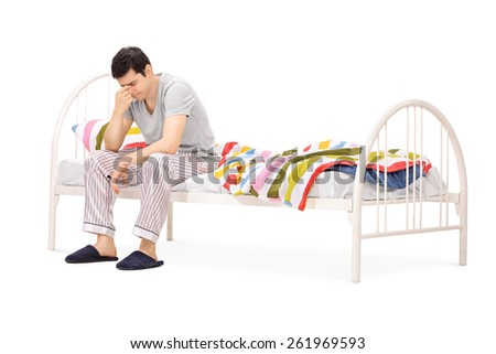 Sad man sitting on a bed and contemplating isolated on white background - stock photo