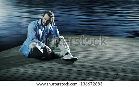 Sad man sitting on a pier - stock photo