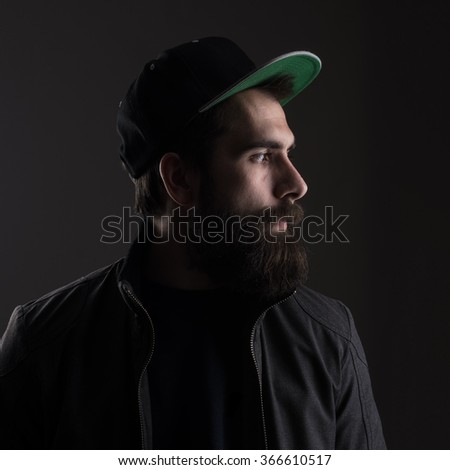 Sad man wearing baseball cap looking away. Low key dark shadow portrait over black background. - stock photo