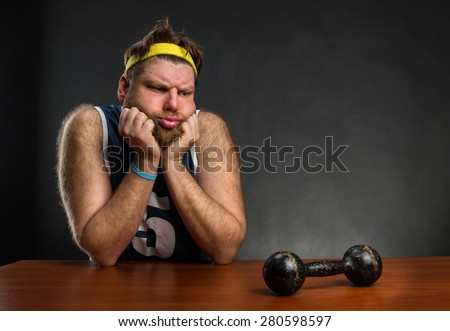 Sad man with a dumbbell - stock photo