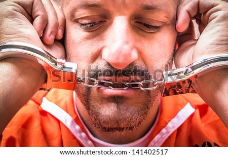 Sad Man with Handcuffs in Prison - stock photo