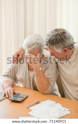 Sad mature couple calculating their domestic bills - stock photo