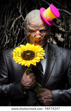 Sad monster in business suit with sunflower - stock photo