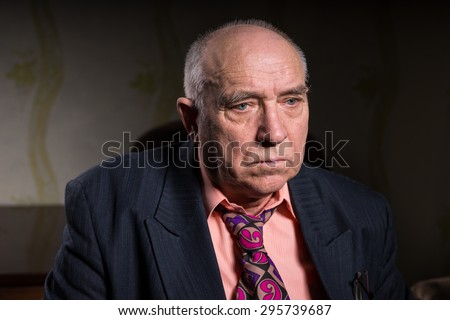 Sad old businessman sitting in his room - stock photo