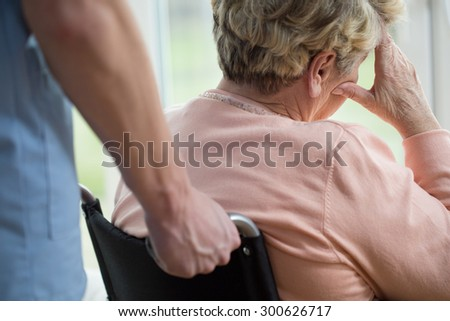 Sad older woman on wheelchair at home - stock photo