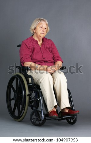 Sad or depressed senior woman in a wheelchair, looking down, studio shot over grey background. - stock photo