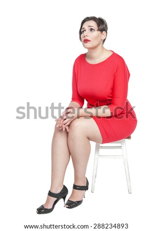 Sad plus size woman sitting on the chair isolated on white background - stock photo
