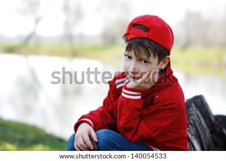 Sad preschool boy in cap sitting at river - stock photo