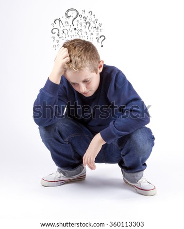 Sad preteen boy sitting on the floor holding his head ,many questions isolated on a white background. Thinking guy  - stock photo