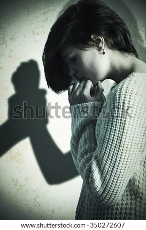 Sad pretty brunette holding her head against silhouette of man grabbing woman - stock photo