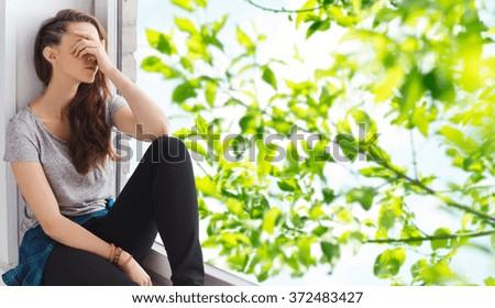 sad pretty teenage girl sitting on windowsill - stock photo