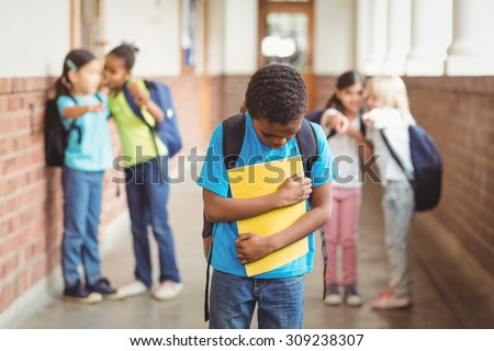 Sad pupil being bullied by classmates at corridor in school - stock photo
