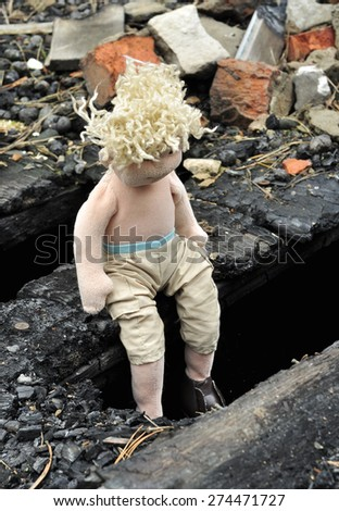 sad rag doll sits in the burnt house - stock photo