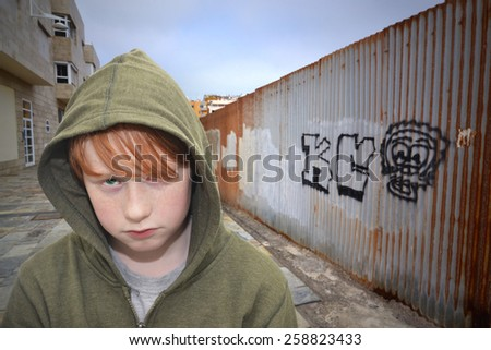 sad redhead boy standing on a lonely street - stock photo