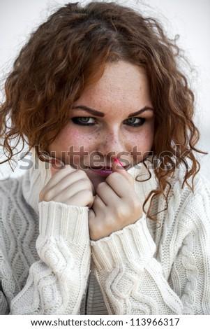 Sad redhead girl in sweater. - stock photo