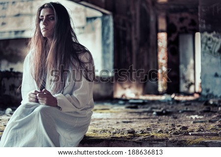 Sad scared schizophrenic anxious  brunette woman in a old abandoned ruined house - stock photo