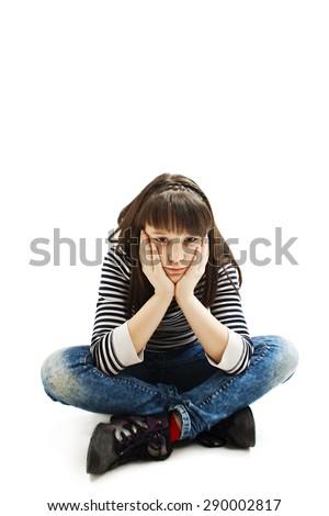 Sad school girl, sitting. Isolated on white background - stock photo