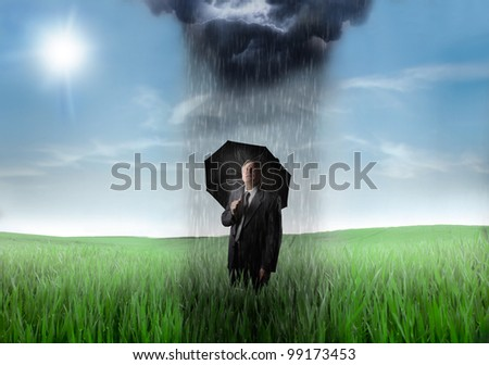 Sad senior businessman on a green meadow with downpour over him and sunny sky in the background - stock photo